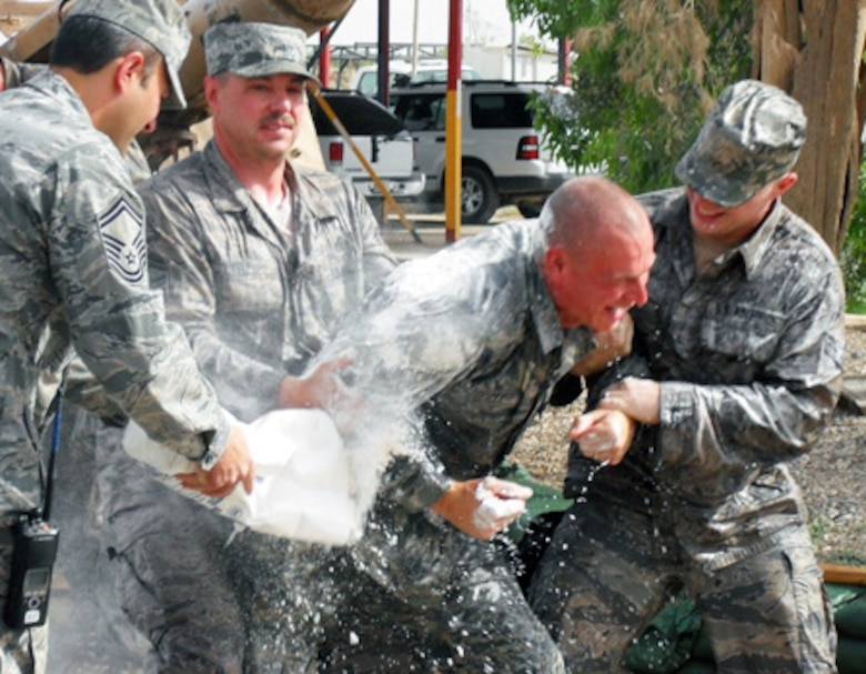 Tech. Sgt. Ted Fussell, 506th Expeditionary Civil Engineer Squadron structural craftsman, gets doused with flour and water during a surprise promotion ceremony for him at Kirkuk Regional Air Base, Iraq, May 21, 2009. Sergeant Fussell is a firefighter with the Anchorage, Alaska, Fire Department, and recently promoted to senior captain. The act of dousing a firefighter with flour and water is a long-standing tradition within the fire department. Sergeant Fussell is a reservist with Air Force Reserve Command's 477th Fighter Group, an F-22 classic associate unit, at Elmendorf Air Force Base, Alaska. (Courtesy photo)