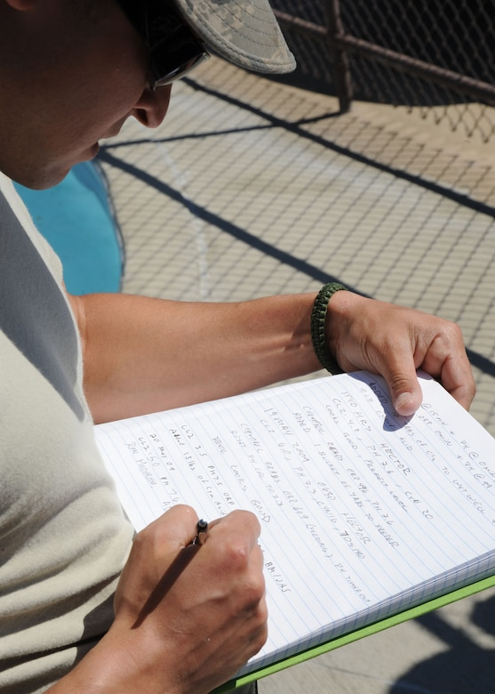 SCOTT AIR FORCE BASE, Ill. -- Sergeant Mayssonet writes down all his completed work in a log book May 20. The log book is a record of the chemicals that were put in the pool as well as the chlorine and pH levels. (U.S. Air Force photo/Airman 1st Class Tristin English)