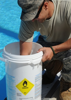 SCOTT AIR FORCE BASE, Ill. -- Staff Sgt. Ben Mayssonet,  375th Civil Engineer Squadron, mixes cyanuric acid for the Fitness Center pool at Scott May 20.  Putting cyanuric acid into the pools holds the chlorine levels, making sure they are not too high or too low. (U.S. Air Force photo/Airman 1st Class Tristin English)