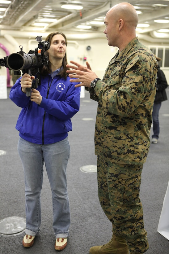 """Jennifer Adams, part of a group of distinguished visitors visiting USS New York, holds a Shoulder-Launched, Multi-purpose Assault Weapon, while Sgt. Nathan Dettling, an infantry assaultman, explains the purpose and function of the weapon system. """"The weight of what you have to carry is incredible!"""" exclaimed Adams, who quickly gave the gear back to Dettling. The Marines are part of Special Purpose Marine Air Ground Task Force 26, a unit formed to support the commissioning of USS New York in New York City, Nov. 7, 2009. With 7 1/2 tons of steel recovered from the World Trade Center forged in her bow, the ship symbolizes America's perseverance in the face of adversity while honoring the memory of those lost, paying homage to the survivors, and building an enduring bond between the ship and the people of the state of New York. The role of SPMAGTF-26 is to represent future Marine expeditionary forces who will deploy on and from a vessel built around the Navy-Marine Corps team. As the newest Landing Platform Dock in the U.S. Navy's fleet, USS New York boasts a larger flight deck and well deck and has many other improvements designed to allow Marines to prepare for and execute missions quicker and more efficiently than previous versions of the LPD. USS New York is scheduled to arrive in New York City, Nov. 2, and will be open to public tours where the embarked Marines will display their gear and interact with visitors."""