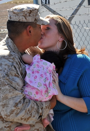 Sgt. Francisco Acosta, Marine Attack Squadron 214 aviation technician, kisses his wife, Aubrey, while holding his newborn, Melody, for the first time after returning to Yuma, Ariz., Nov. 1, 2009, from a six-month deployment to Afghanistan. An advanced party of approximately 20 Marines came home early from deployment to prepare for the remainder of the squadron, scheduled to return by Thanksgiving.