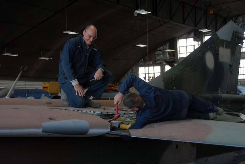 DAYTON, Ohio - Members of the 315th Maintenance Squadron out of Charleston Air Force Base, S.C., work to remove a wing from a MiG-23 during their two-week stay at Wright-Patterson Air Force Base, Ohio, where the group worked in the restoration hangar at the National Museum of the U.S. Air Force. (U.S. Air Force photo)