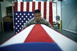 Tech. Sgt. Willard Rico tightens a U.S. flag over a casket in practice for a dignified transfer of remains. The AFMAOC is the Defense Department's only joint-service mortuary in the continental United States. (U.S. Air Force photo/Staff Sgt. Bennie J. Davis III)