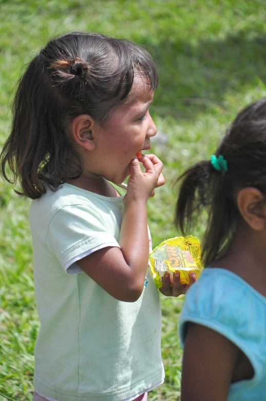 SOTO CANO AIR BASE, Honduras – A child of El Ciruelo, a remote mountain village near Comayagua, Honduras, eats a piece of candy Oct 31. Eighty-one volunteers from Joint Task Force-Bravo hiked more than five miles up and down a rocky, mountain road to deliver food to the remote village. The volunteers carried a total of 122 bags of food, equaling 2,684 pounds. Each bag of food was intended to go to one of the families of this poor mountain village, and included vegetable oil, ketchup, pasta, a couple cans of sardines and bags of sugar, rice, flour and beans (U.S. Air Force photo/Staff Sgt. Chad Thompson).