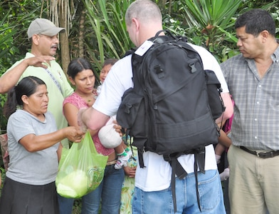 SOTO CANO AIR BASE, Honduras – Air Force Maj. Rick Schott, medical element anesthesiologist, hands a bag filled with food to some villagers of El Ciruelo, a remote mountain village near Comayagua, Honduras, Oct 31 for a monthly chapel hike. Eighty-one volunteers from Joint Task Force-Bravo hiked more than five miles up and down a rocky, mountain road to deliver food to the remote village. The volunteers carried a total of 122 bags of food, equaling 2,684 pounds. Each bag of food was intended to go to one of the families of this poor mountain village, and included vegetable oil, ketchup, pasta, a couple cans of sardines and bags of sugar, rice, flour and beans (U.S. Air Force photo/Staff Sgt. Chad Thompson).