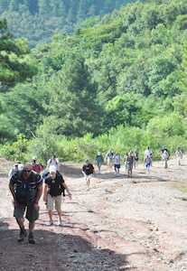 SOTO CANO AIR BASE, Honduras – Volunteers climb a steep grade of mountain road near Comayagua, Honduras Oct. 31 for a monthly chapel hike. Eighty-one volunteers from Joint Task Force-Bravo hiked more than five miles up and down a rocky, mountain road just outside of Comayagua, Honduras to deliver food to a remote village. The volunteers carried a total of 122 bags of food, equaling 2,684 pounds. Each bag of food was intended to go to one of the families of this poor mountain village, and included vegetable oil, ketchup, pasta, a couple cans of sardines and bags of sugar, rice, flour and beans (U.S. Air Force photo/Staff Sgt. Chad Thompson).
