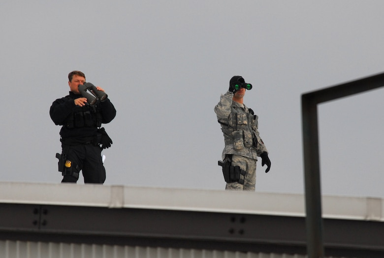 Staff Sgt. Anthony Rook (right), security forces member at the 115th Fighter Wing in Madison, Wis., along with a Secret Service agent scan for potential threats prior to and during a presidential visit Nov. 4, 2009.  President Barack Obama landed at the Air National Guard base on his way to give a speech at Madison's James Wright middle school about education reform.  President Obama's visit marks the first time that a sitting president has visited the base. (U.S. Air Force Photo by Master Sgt. Dan Richardson)