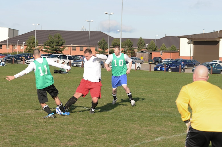 RAF MILDENHALL, England -- Nick Giannopoulos (red shorts), 352nd Maintenance Squadron, tackles Daniel Crane (11), 100th Security Forces Squadron, while Daniel Baker (10), looks on during an intramural soccer match Nov. 4. The 100th SFS took the game 3-2 at the Hardstand Fitness Center.  (U.S. Air Force photo/Senior Airman Thomas Trower)