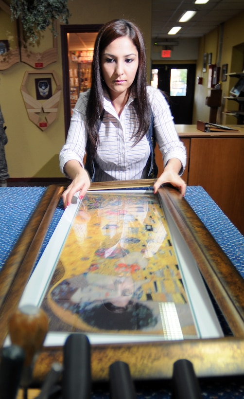 Deniz Yara, Arts and Crafts Center's framing specialist, frames a painting for a customer at the ACC Tuesday, Nov. 3, 2009 at Incirlik Air Base, Turkey. The framing specialist can teach customers how to frame, frame for them, or even build custom frames. They also offer shadowboxes and retirement gifts inside the shop. (U.S. Air Force photo/Senior Airman Sara Csurilla)
