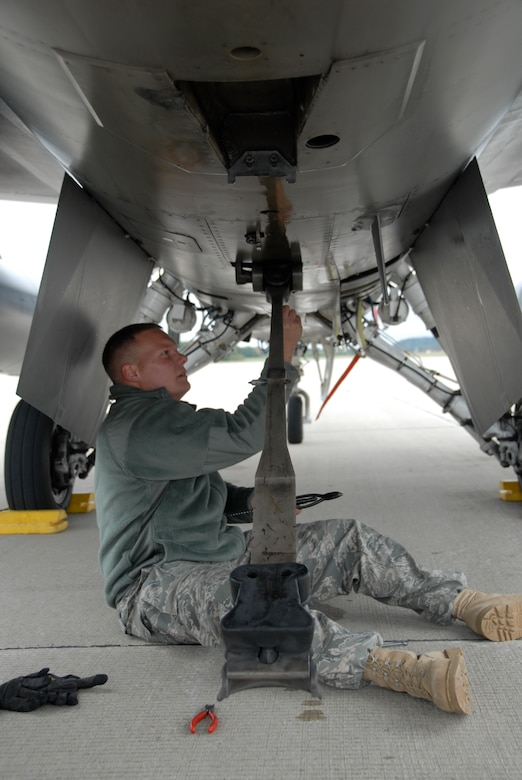 "Staff Sgt. Jordan Jensen, a crew chief with the115th Fighter Wing in Madison, Wis., resets the tail hook on an F-16 Fighting Falcon that is used to ""hook"" the Barrier Arresting Kit 12  cable installed at the end of each runway, a system designed to stop an aircraft."