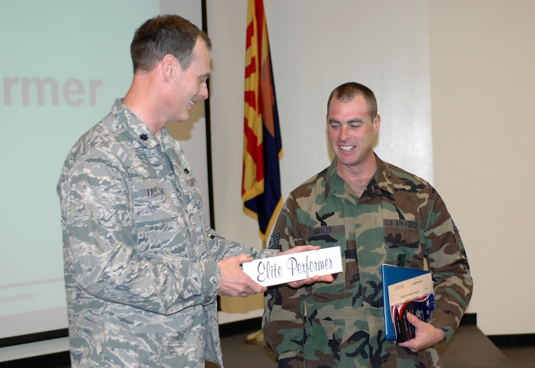 Tech. Sgt. John Mahler,148th Figther Squadron, receives the Elite Performer award from Lt. Col. James Taylor, 162nd Maintenance Group Commander, Nov. 6. Sergeant Mahler was choosen for the award from 800 Guardsmen that serve in the maintenance group here. The award recognizes maintainers who consistently perform quality work, maintain safe work practices, follow technical data, and engage in quality initiatives. (Air National Guard photo by Maj. Gabe Johnson).