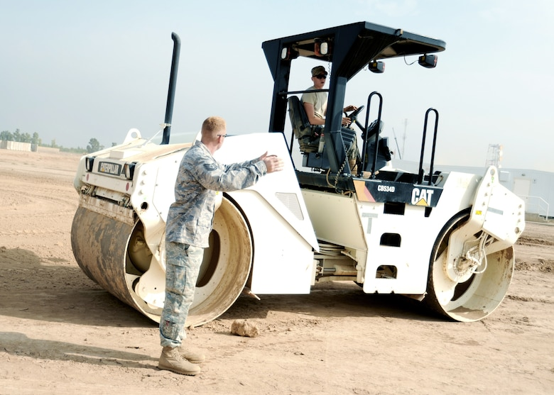 JOINT BASE BALAD, Iraq -- Tech. Sgt. Orlin Rohde, 732nd Expeditionary Civil Engineer Squadron heavy equipment operator and project manager, directs Airman Marshall Hess as he drives a vibratory roller to prepare the grounds for a new container repair yard Nov. 2, 2009. By using containers repaired here instead of purchasing new ones, the projected savings total more than $100 million as military assets withdraw from Iraq. (U.S. Air Force photo/Senior Airman Christopher Hubenthal)