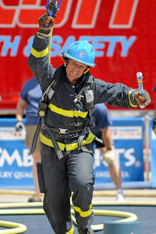 U.S. Air Force Academy firefighter Ron Prettyman hauls a loaded fire hose over his shoulder as he sprints forward to finish in the over-40 male relay at a firefighter combat challenge held at the Academy June 27, 2009. Mr. Prettyman is one of five firefighters who will compete at the World Firefighter Challenge XVIII, scheduled to be held in Las Vegas Nov. 16-20. (U.S. Air Force photo/Mike Kaplan)