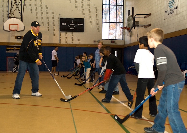 HANSCOM AIR FORCE BASE, Mass. – Boston Bruins alumnus Tommy Songin shows Hanscom children some fundamental stick maneuvers during an Air Force Family Week street hockey event at the Hanscom Youth Center, Nov. 4, sponsored by the Boston Bruins. Bruins staff led Hanscom children through a number of street hockey drills focusing on the fundamentals of play. The Bruins donated all of the street hockey equipment to Hanscom's Youth Center so children could continue to enjoy the game. (U.S. Air Force photo by Walter Santos)