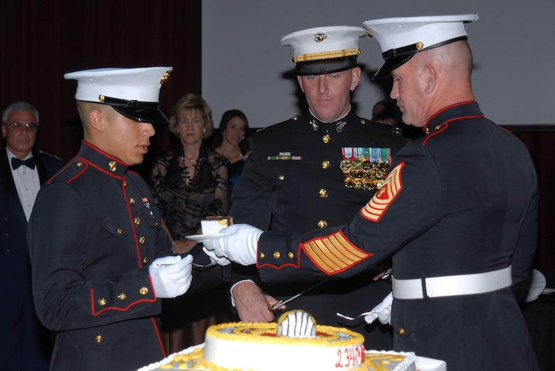 SAN ANGELO, Texas -- Marine Corps Master Gunnery Sgt. Peter Bordeleau, hands the second piece of cake to Marine Corps Pvt. A. H. Peralta at the 234th Marine Corps Birthday Ball hosted by the Marine Corps Detachment, Goodfellow Air Force Base, Nov. 7, 2009. The first piece of cake is given to the guest of honor, the second to the oldest Marine present. Upon receiving the second piece of cake, the oldest Marine will in turn pass it on to the youngest Marine present, signifying the passing of experience and knowledge from the old to the young of the Corps. (U.S. Air Force photo/Staff Sgt. Laura R. McFarlane)