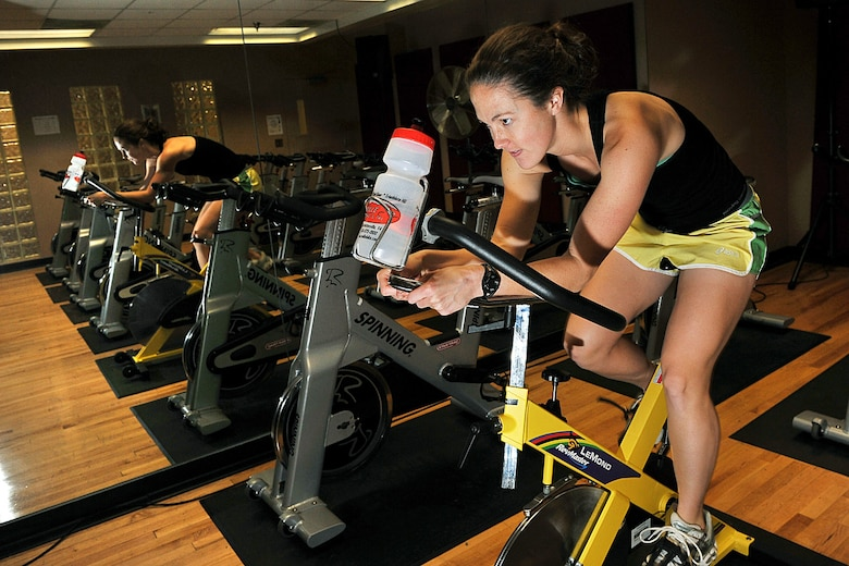 OFFUTT AIR FORCE BASE, Neb. -- Second Lt. Lindsey Myhr, 55th Maintenance Squadron accessory flight commander, pedals a bicycle inside the Offutt Field House here Nov. 5 in preparation for her next triathlon. A basic triathlon event consists of a 1.5-km swim, a 40-km bike ride and a 10-km run. The biggest triathlon event, the Iron Man challenge, consists of a 2.4 mile swim, 112 miles on bike, and a 26.2 mile run.  U.S. Air Force photo by Charles Haymond