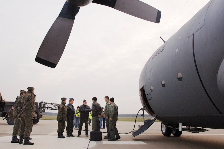 Capt. Tyler Robertson, Capt Ryan Donohoe and Staff Sgt. Eric Kleser are greeted by Polish air force's 33rd Air Base Commander Brig. General Tadeusz Mikutel (fourth from right) and 14th Air Transport Squadron Commander Lt. Col. Mieczyslaw Gaudyn Nov. 2, 2009, at Powidz Air Base, Poland. The aircraft and crew, from Ramstein Air Base, Germany, delivered the C-130 to Poland as part of a program for building partnership capacities between the United States and Poland. Captain Robertson is an aircraft commander, Captain Donohoe is a navigator, and Sergeant Kleser is a flight engineer. (Defense Department photo/Master Sgt. Scott Wagers)