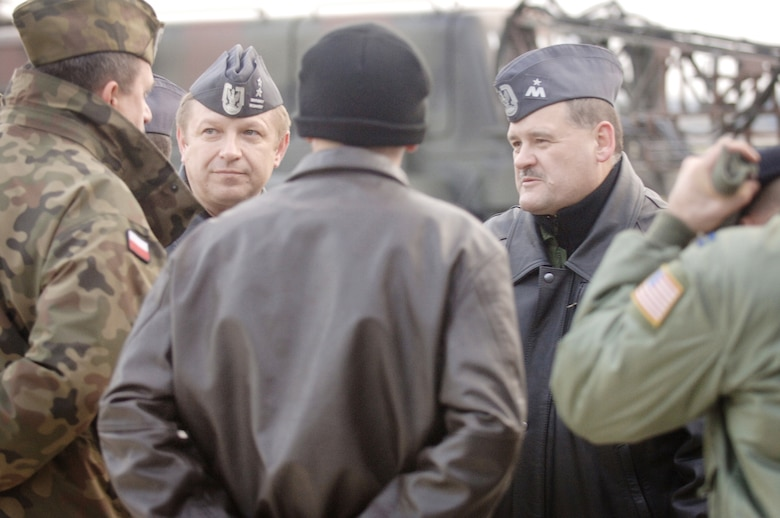 American Airmen talk to Polish air force Brig. Gen. Tadeusz Mikutel (second from left) and Polish air force Lt Col Mieczyslaw Gaudyn (right) after delivering a C-130E Hercules from Ramstein Air Base, Germany, to its final destination Nov. 2, 2009, at Powidz Air Base, Poland. General Mikutel is the Polish air force's 33rd Air Base commander, and Colonel Gaudyn is the 14th Air Transport Squadron commander. The Ramstein AB aircraft and crew, from the 37th Airlift Squadron, delivered the second U.S. Air Force C-130E to Poland as part of a program for building partnership capacities amongst United States allies. (Defense Department photo/Master Sgt. Scott Wagers)