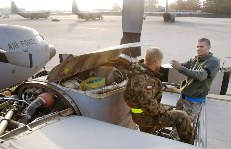 Staff Sgt. Matthew Parker works with Polish air force Chief Warrant Officer Daniel Orlowski in tracing an electrical problem on the No. 4 engine of the last in a series of E-model C-130 Hercules aircraft Oct. 29, 2009, at Ramstein Air Base, Germany. The two mechanics, assigned to the 86th Aircraft Maintenance Squadron and 33rd Air Base Group, respectively, were completing a week-long home station check before the aircraft is transferred to the Polish air force's 14th Airlift Squadron at Powidz Air Base, Poland, as part of a program for building partnership capacities between the United States and its allies. (Defense Department photo/Master Sgt. Scott Wagers)