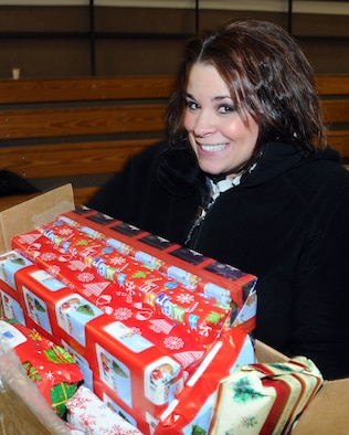 KBRJ's morning disk jocky DeAnna hauls a load of Christmas gifts for the kids at the St. George School. DeAnna volunteered to travel to St. George to serve as master of ceremonies for the Operation Santa Claus visit. U.S. Air Force photo by 1st Lt. John Callahan.