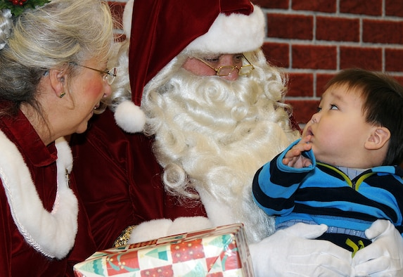 St. George resident Till Lekanof, age 1, gets some personal attention from Santa and Mrs. Santa during an Operation Santa Claus mission on Nov. 7, 2009. U.S. Air Force photo by 1st Lt. John Callahan.