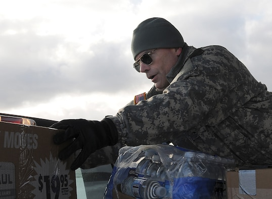 Brig. Gen. Thomas Katkus, then the acting adjutant general of the Alaska National Guard, stacks groceries in a pickup truck for transport to the St. George School. Gen. Katkus was named the Alaska National Guard's adjutant general three days later. U.S. Air Force photo by 1st Lt. John Callahan.