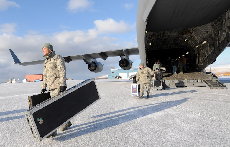 MSgt. Ron Larsen, a pianist with the Elmendorf-based Air Force Band of the Pacific, hauls gear off the C-17 that transported the band members and Operation Santa Claus volunteers to St. George. Assisting him as roadie is Lt. Col. Richard Cavens, wing chaplain for the Alaska Air National Guard's 176th Wing. U.S. Air Force photo by 1st Lt. John Callahan.