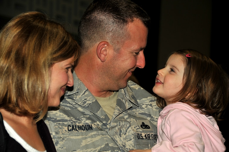 Senior Master Sgt. Jarrett Calhoun, an Aircraft Mechanics Supervisor with the 115th Fighter Wing in Madison, Wis., holds his wife Sara and daughter Leah after returning home from a two month deployment to Iraq Nov. 12, 2009. The unit deployed approximately 200 members as part of its scheduled Air Expeditionary Force rotation. (U.S. Air Force photo by Master Sgt. Dan Richardson)