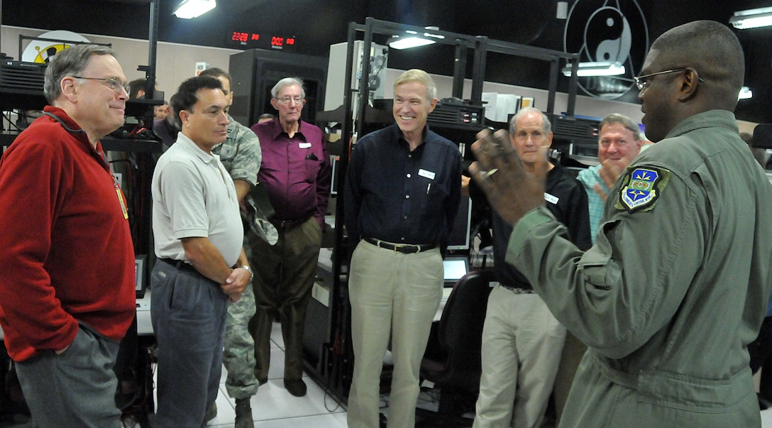 Master Sgt. Timothy Teamer, right, 705th Combat Training Squadron, gives a briefing to retired Air Force Chief of Staff Gen. John Jumper, left, and others about a high tech program and the equipment associated with it, Nov. 6. General Jumper was taking a tour of the Distributed Mission Operations Center and was here as the guest speaker for their 30 Anniversary dinner later that evening.  U.S. Air Force photo by Todd Berenger