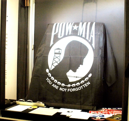 Articles in this display include a pre-addressed postcard to Ton Duc Thang, the president of North Vietnam, to enlist his support in determining the fate of Lt. Larry Potts at the National Museum of the U.S. Air Force in Dayton, Ohio. Despite repeated appeals like this one, North Vietnam remained unsympathetic. The black flag is the official POW/MIA flag, which is flown six times a year at designated federal sites. It was designed in 1971 by Newt Heisley, a World War II pilot and advertising artist who never profited from the uncopyrighted design. (U.S. Air Force photo)
