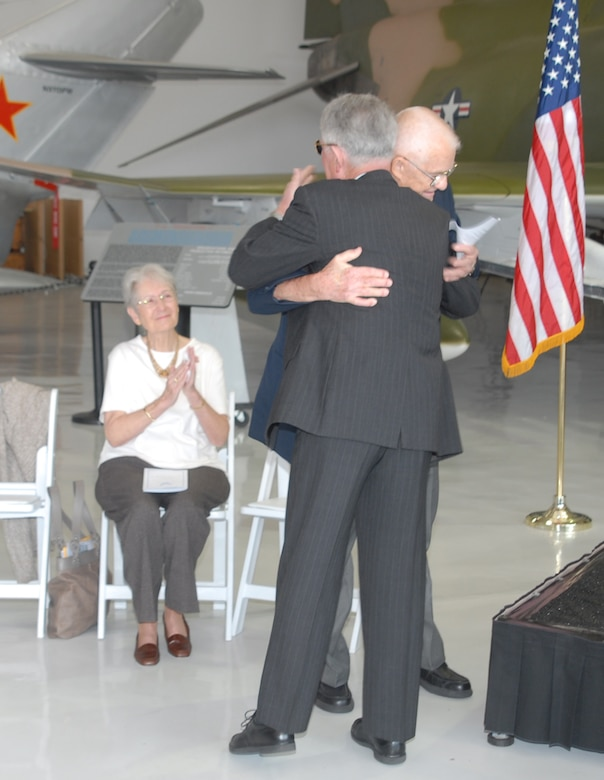 Retired Col. James Hivner and retired Navy Cmdr. Rick Tolley embrace Nov. 11 at the Cavanaugh Flight Museum in Addison, Texas, as Phyllis Hivner looks on.  Commander Tolley had taken on the task of finding the owner of a wedding ring that had been confiscated by North Vietnam soldiers from an American prisoner of war in 1965.  The ring had been found recently in Vietnam and eventually passed to Commander Tolley who searched for its owner until he found Colonel Hivner.  Family, friends and Airmen from Sheppard Air Force Base, Texas, traveled to the museum to witness the return of the ring.  (U.S. Air Force photo/LouAnne Sledge)