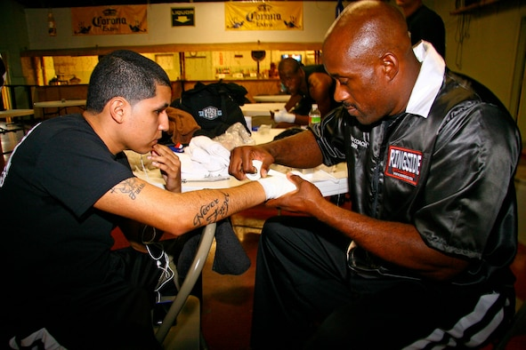 Tinker head coach Lavell Sims, right, tapes the hands of boxer Jose Robles several minutes before his fight Nov. 7 in Tulsa. Sims was pleased with his fighters' performance Saturday, but will be pushing his boxers to the limit in preparing for their home bout Nov. 20 at the Gerrity Fitness and Sports Center. (Air Force photo by John Stuart)