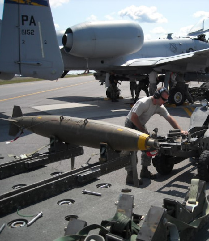Tech. Sgt. Dennis L. Donahue, 111th Aircraft Maintenance Squadron, Pa. Air National Guard, preps a live MK-82 low drag bomb before it is lifted and attached to an A-10 aircraft, during live loading operations at Fort Drum, NY.