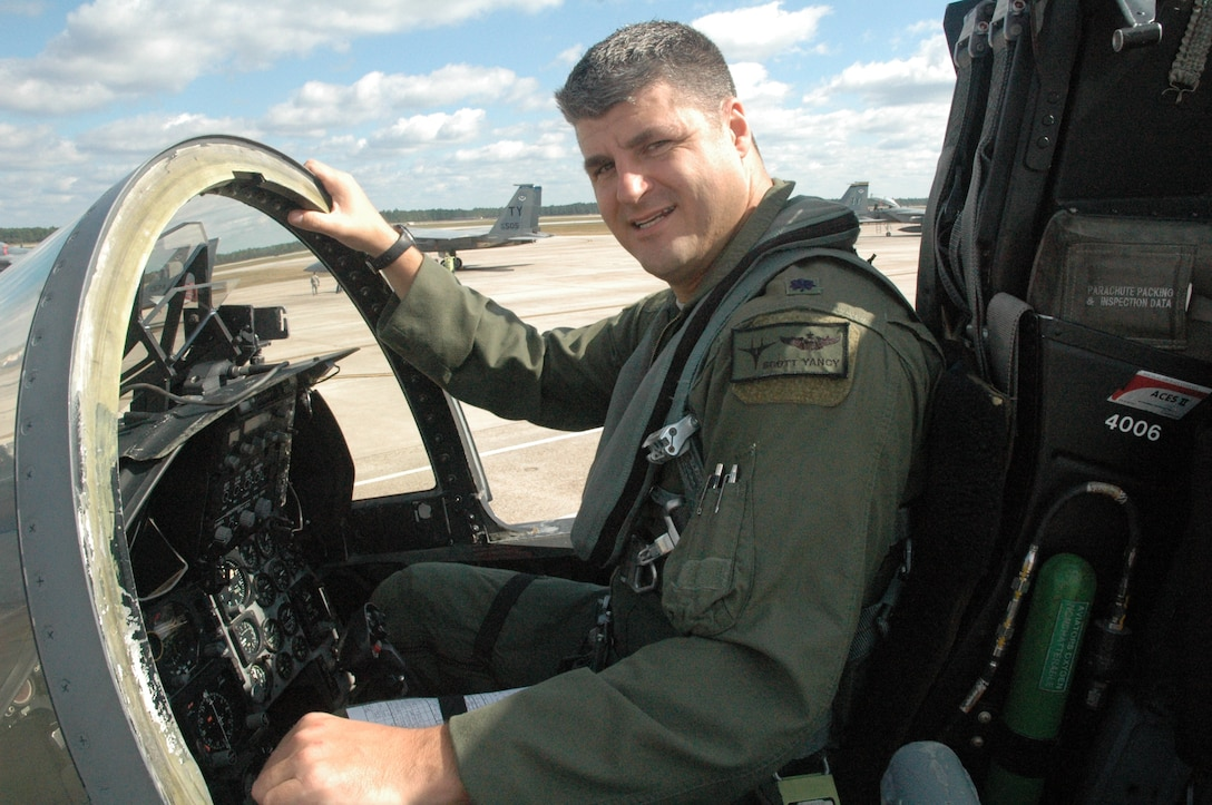 Lieutenant Colonel Scott Yancy, 95th Fighter Squadron Commander poses in his part-time office-the cockpit of an F-15C. (U.S. Air Force photo by Major Veronica Kemeny)