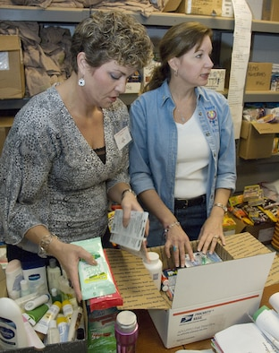 Ann Marie Bernick (left) and Nancy Muscatell, volunteers for the 403rd Wing Key Family Member Program, pack care packages Nov. 7, 2009, at Keesler Air Force Base, Miss. The supplies are for wing reservists deployed overseas. (U.S. Air Force photo/Tech. Sergeant Ryan Labadens)