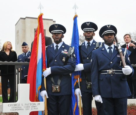 SPANGDAHLEM AIR BASE, Germany -- From left to right, Senior Airmen Jason Myers, Brandon Jackson, and Jerrime Williams, 702nd Munitions Support Squadron Color Guard members, stand at attention in front of the gravestone of Gen. George S. Patton Jr., Third Army commander during World War II, during the annual Veterans Day ceremony at the Luxembourg American Cemetery and Memorial in Luxembourg City Nov. 11. The 50.5 acre cemetery, which is one of 14 American cemeteries established overseas after World War II, contains the remains of more than 5,000 American servicemembers who died fighting in World War II. (U.S. Air Force photo/Maj. Jillian Torango)