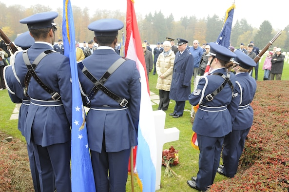 SPANGDAHLEM AIR BASE, Germany -- The 702nd Munitions Support Squadron Color Guard from Buechel Air Base, Germany, stands at attention by the grave of Gen. George Smith Patton, Third Army commander during World War II, as Helen Patton-Plusczyk, General Patton's granddaughter, and Col. Tip Wight, 52nd Fighter Wing commander, pay their respect to the soldiers who died fighting in World War II during the annual Veterans Day ceremony at the Luxembourg American Cemetery and Memorial in Luxembourg City Nov. 11. The 50.5 acre cemetery is one of 14 American cemeteries established overseas after WWII and contains the remains of more than 5,000 American servicemembers who died fighting the second world war. (U.S. Air Force photo/Maj. Jillian Torango)