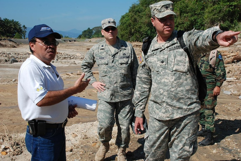 ILOPANGO, El Salvador—Air Force Lt. Col. Anthony Higdon and Army Lt. Col. Jose Gierbolini, engineers from U.S. Southern Command, discuss damage assessment with a representative of El Salvador's Ministry of Public Works Nov. 13. The combined U.S., Salvadoran damage assessment team is working together to gather data from areas with damaged by flooding and landslides. Joint Task Force-Bravo, based out of Soto Cano Air Base, Honduras, has been helping in El Salvador since Nov. 11, providing humanitarian assistance and disaster relief to flood-damaged communities (U.S. Air Force photo/1st Lt. Jennifer Richard).