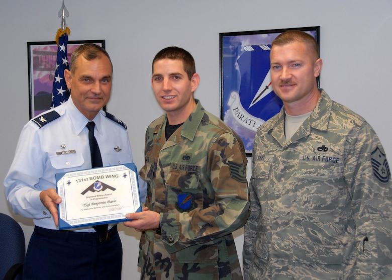 Col. Robert Leeker, 131st Bomb Wing commander, presents Tech. Sgt. Benjamin Davis, 131st Aircraft Maintenance Squadron aerospace maintenance technician, the Diamond Sharp Award for November UTA. (Photo by Master Sgt. Mary-Dale Amison)
