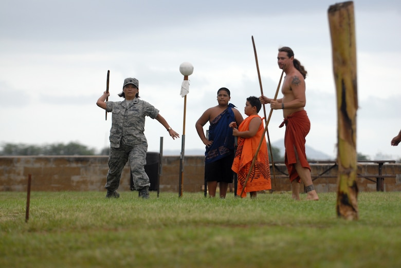 HICKAM AIR FORCE BASE, Hawaii -- Lt. Col. Tracey Saiki, 15th Airlift Wing public affairs, attempts to throw a spear into a trunk during the O'o Ihe event at the Makahiki Festival here, Nov. 14. For more than two-thousand years, the significance of Lono and his contributions to the beliefs and practices of the early Hawaiian people, influenced the celebration of events held during the Makahiki Festival throughout the Hawaiian Islands. Since Lono was the embodiment of all the characteristics of peace and welfare, all warfare was strictly forbidden during the time of the Makahiki. Since Lono represented the spiritual life-force that came out of all agricultural efforts, much feasting of every kind was done during the four months of the Makahiki. This focus on health and welfare made games of skill that tested a healthy body and mind a focal point of the Makahiki games. (U.S. Air Force photo/Senior Airman Gustavo Gonzalez)