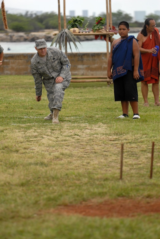 HICKAM AIR FORCE BASE, Hawaii -- Chief Master Sgt. Craig Recker, 15th Airlift Wing command chief, attempts to roll a rock through two sticks as part of a game during the Makahiki Festival here, Nov. 14. For more than two-thousand years, the significance of Lono and his contributions to the beliefs and practices of the early Hawaiian people, influenced the celebration of events held during the Makahiki Festival throughout the Hawaiian Islands. Since Lono was the embodiment of all the characteristics of peace and welfare, all warfare was strictly forbidden during the time of the Makahiki. Since Lono represented the spiritual life-force that came out of all agricultural efforts, much feasting of every kind was done during the four months of the Makahiki. This focus on health and welfare made games of skill that tested a healthy body and mind a focal point of the Makahiki games. (U.S. Air Force photo/Senior Airman Gustavo Gonzalez)