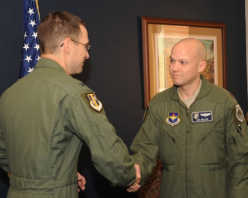 Col. C. K. Hyde, 314th Airlift Wing commander, presents Maj. Joe Miller, 314th Airlift Wing chief of plans, with a coin Nov. 13 for his work as a project officer during a recent visit by the Air Education and Training Command civil engineer, Col. Mark Correll. (U.S. Air Force photo by Staff Sgt. Chad Chisholm)