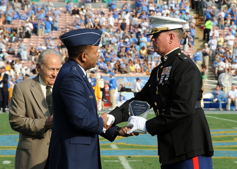 "Brig. Gen.  Samuel Greaves (center), Space and Missile Systems Center vice commander, presents the ""2009 Veteran of the Year"" award to Marine Corp Lt. Col. David McCarthy (right) during the halftime ceremony at the UCLA Veterans and Military Appreciation football game held at the Rose Bowl Stadium, Pasadena, Nov.  7.  Army Reserve Ambassador Emeritus Ronald Markarian (left), California State Director of the U.S. Selective Service System, also participated in the ceremony. The UCLA Bruins won the game played against the Washington Huskies.  (Photo by Lou Hernandez)"