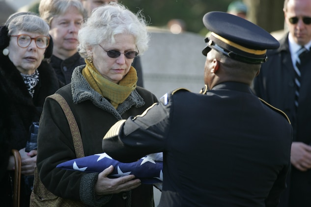 NEW YORK -- An Army soldier presents an American Flag to Debra Allee, the niece of the formerly oldest living female Marine, Miriam Cohen, who was buried Nov. 17, in Cypress Hills National Cemetery in honor of Cohen's service to her country. The 101-year-old Cohen enlisted in the Marine Corps during World War II and again during the Korean War. She was the oldest female enlistee of her time at 35 years old and was part of the first female Marine recruit class. (Official Marine Corps photo by Sgt. Randall A. Clinton)
