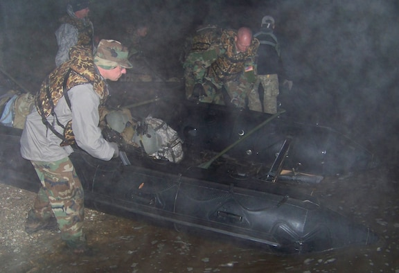 Tech. Sgt. Jason Rushing (left) and Tech. Sgt. Charles Smith (center), both combat aviation advisors with the 19th Special Operations Squadron, prepare a row boat for travel during the Raven Claw field exercise at the Eglin range Nov. 5. The boats were used during part of a 20-mile expedition across the Eglin range at night. (Air Force photo by Airman 1st Class Joe McFadden.)