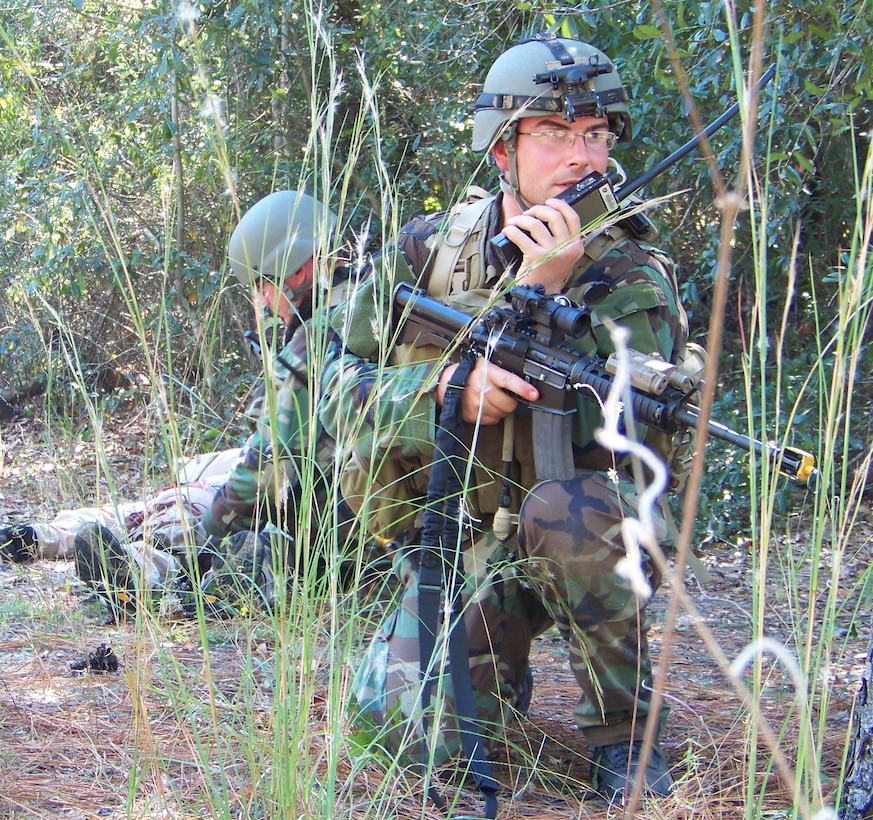 Capt. Brian Daniels (front), 19th Special Operations Squadron, communicates with personnel while Tech. Sgt. Jason Rushing (back), 19th SOS, checks the vital signs of a wounded indigenous force during the Raven Claw field exercise at the Eglin range Nov. 5. Airmen worked with partner-nation forces about recovery tactics and medical treatment. (Air Force photo by Airman 1st Class Joe McFadden.)