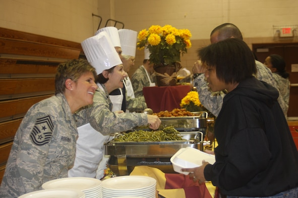 WRIGHT-PATTERSON AIR FORCE BASE, Ohio - Two reservists from the 445th Airlift Wing volunteered at the base's annual Airman's Homestyle Thanksgiving dinner Nov. 17 at the Jarvis Gym.  Lt. Col. Linda Stokes-Crowe, 445th Aeromedical Evacuation Squadron commander, and Chief Master Sgt. Peri Rogowski, 445th Airlift Wing command chief, sported chefs hats and aprons to serve Thanksgiving meals alongside commanders, first sergeants, and other volunteers from across the base to single/unaccompanied Airmen and family members of deployed personnel.  Sponsored by the 88th Air Base Wing Chaplain's office, and coordinated by Chaplain (Capt.) William Spencer, 88th ABW chaplain's office, Airmen enjoyed a night of music from the U.S. Air Force Band of Flight, and a home-style cooked Thanksgiving dinner prepared by the Wright-Patterson Club. (U.S. Air Force photo/Stacy Vaughn)