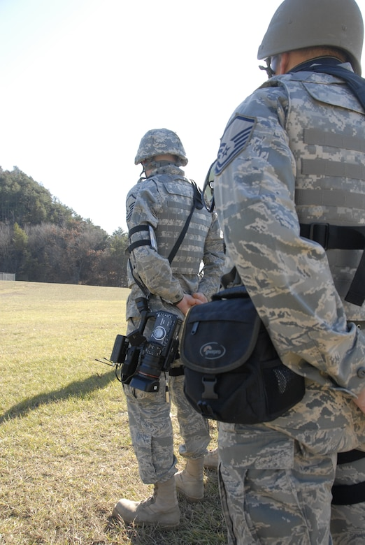 Master Sgt. Paul Gorman (right), along with Master Sgt. Dan Richardson, public affairs personnel from the 115th Fighter Wing in Madison, Wis., form up for roll call during a Security Forces exercise at Volk Field Combat Readiness Training Center Nov. 7, 2009. Three public affairs personnel from the 115th embedded with their own Security Forces to learn how to effectively operate under the pressures of a combat environment.  The training proved beneficial to both sides as SF members learned ways to protect embedded assets while performing their regular duties.  (U.S. Air Force Photo by Tech. Sgt. Don Nelson)