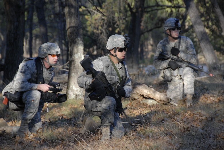 Master Sgt. Dan Richardson (left), broadcaster with the 115th Fighter Wing in Madison, Wis., looks on as Senior Airmen Nathan Ortiz (middle) and Tech Sgt. Kirk Flatten, Security Forces members assess a possible threat during a Security Forces exercise at Volk Field Combat Readiness Training Center Nov. 7, 2009. Three public affairs personnel from the 115th embedded with SF to learn how to effectively operate under the pressures of a combat environment.  The training proved beneficial to both sides as SF members learned ways to protect embedded assets while performing their regular duties.  (U.S. Air Force Photo by Tech. Sgt. Don Nelson)