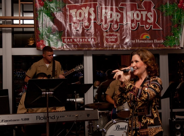 The U.S. Marine Corps Forces, Pacific Band accompanies local entertainer Anita Hall as she sings holiday tunes during a Toys for Tots corporate sponsors' reception at the First Hawaiian Bank building here Nov. 19. Sponsors were presented with plaques to thank them for their contributions to the Marine Corps Reserve's Toys for Tots program.